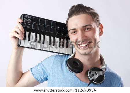 Portrait of young smiling deejay with headphones and midi keyboard on his shoulder.Piercing near mouth.