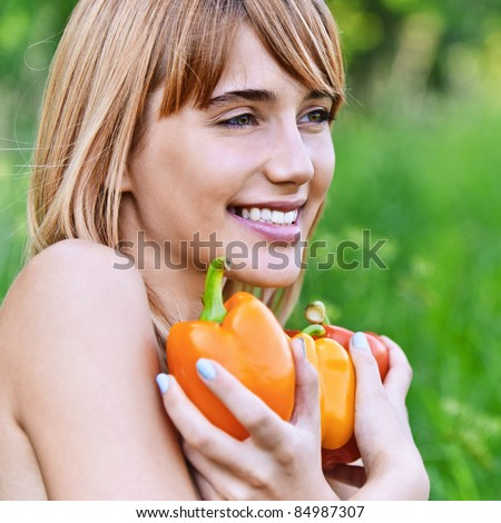 Portrait of young smiling fair-haired woman holding several vegetables and looking somewhere at summer green park. - stock photo