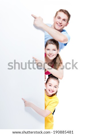 Portrait of young smiling family pointing by finger to the banner - isolated on a white background.