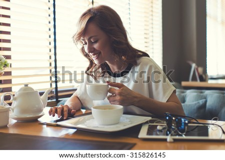Portrait of young smiling female speak with her friends while chatting on mobile phone device during breakfast in coffee shop, caucasian attractive happy woman read text message on her cell telephone - stock photo
