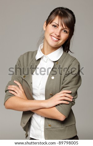 Portrait of young smiling female standing with folded hands, over grey background