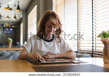 Portrait of young smiling female using touch pad in headphones while calling on video to her boyfriend, happy attractive woman looking funny videos while browsing internet pages on her digital tablet - stock photo
