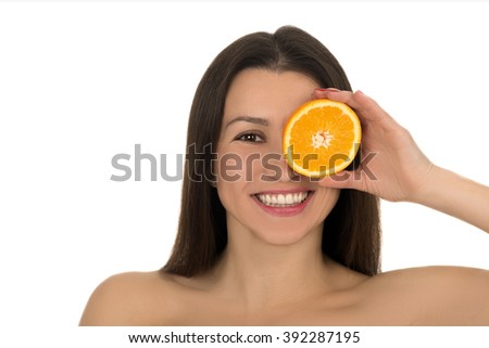 portrait of young smiling girl on a white background with half orange in hand. minerals and vitamins. healthy food concept. skin care and beauty