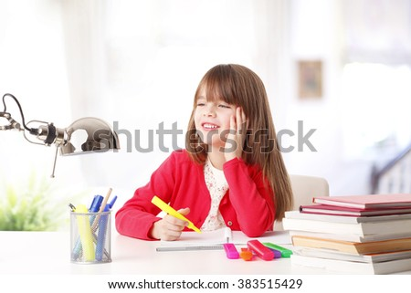 Portrait of young smiling girl studying at her desk at home.