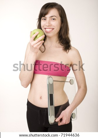 portrait of young smiling girl with green apple and scales