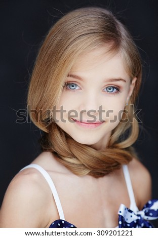 Portrait of young smiling girl with long blond hair and blue eyes. - stock photo