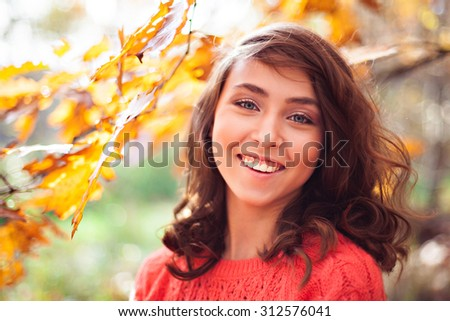 Portrait of young smiling girl with long hair in the autumn forest in sunny day - stock photo