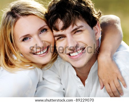 portrait of young smiling happy beautiful couple on nature