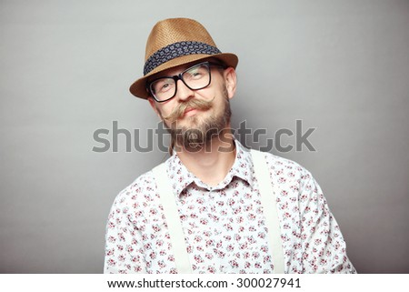 Portrait of young smiling hipster isolated on grey background