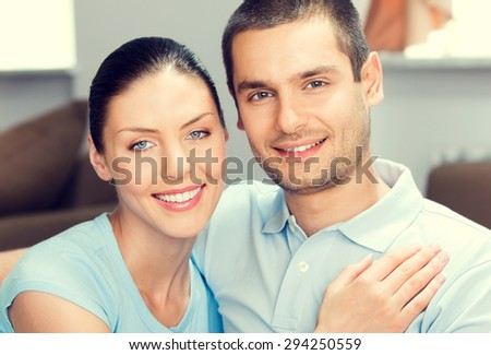 portrait of young smiling lovely couple in blue casual smart clothing, at home - stock photo