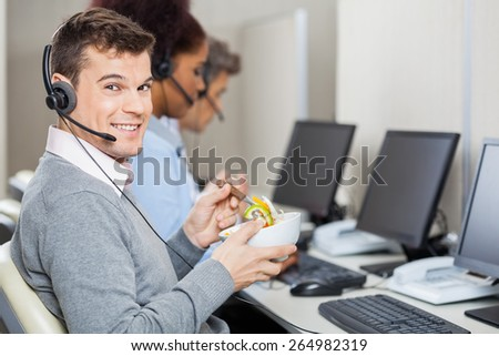 Portrait of young smiling male customer service representative having food while colleagues working in office - stock photo