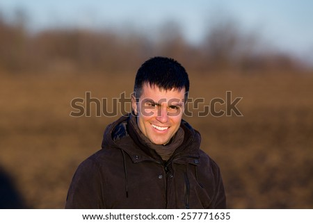 Portrait of young smiling man in jacket in park - stock photo