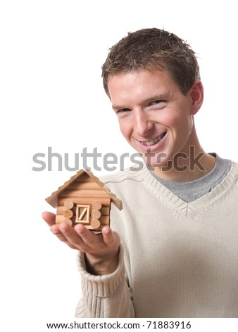 portrait of young smiling man showing a tiny cabin isolated on white background - stock photo