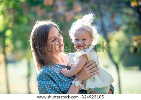 Portrait of young smiling mother holding cute happy toddler daughter wearing dress, hugging, looking at baby with love and adoration, walking together in park in warm sunny weather - stock photo