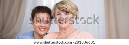 Portrait of young smiling nurse with her aged happy patient - stock photo