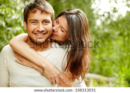 Portrait of young smiling people embracing tenderly and bonding - stock photo