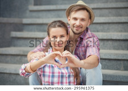 Portrait of young smiling people embracing tenderly and bonding. Man and woman making heart with their hands. - stock photo