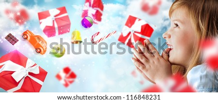 Portrait of young smiling praying girl looking up against sky background. Red gift boxes and toys are flying around - stock photo
