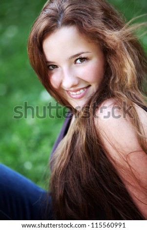 Portrait of young smiling redhaired girl relaxing in the park - stock photo