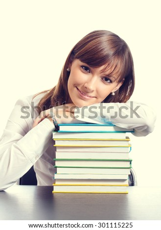 Portrait of young smiling student or businesswoman with textbooks - stock photo