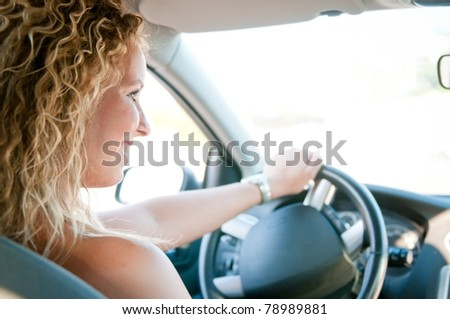 Portrait of young smiling woman driving car - stock photo