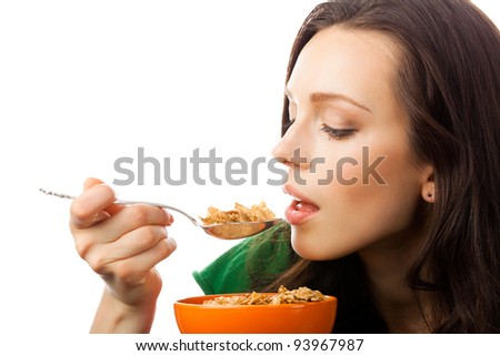 Portrait of young smiling woman eating muesli or corn flakes, isolated over white background