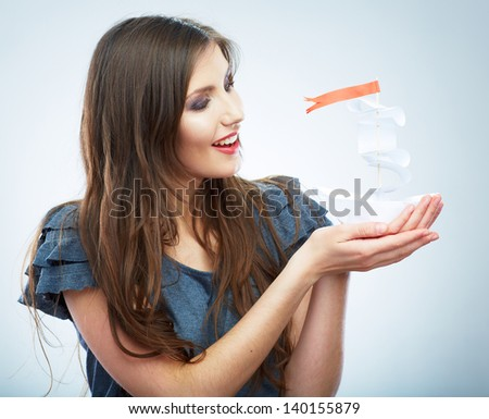 Portrait of young smiling woman hold white paper ship. Female model isolated studio portrait. - stock photo