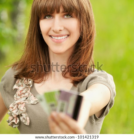 Portrait of young smiling woman holding several credit cards at summer green park - stock photo