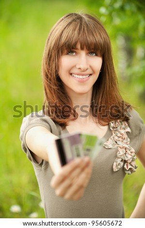 Portrait of young smiling woman holding several credit cards at summer green park