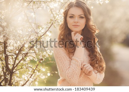 Portrait of Young smiling woman in blooming spring trees. outdoors portrait. Soft sunny colors.Close portrait. - stock photo