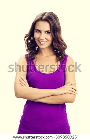 Portrait of young smiling woman in casual smart lilac clothing with crossed arms - stock photo
