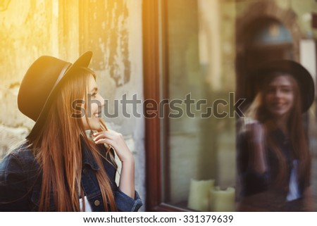 Portrait of young smiling woman looking at the shop window. Toned  - stock photo