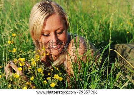 portrait of young smiling woman lying on the grass - stock photo