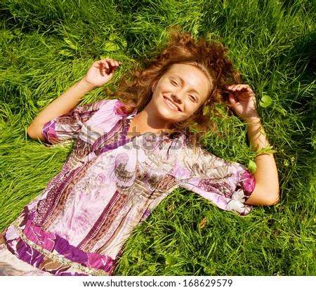 portrait of young smiling woman on the grass  - stock photo