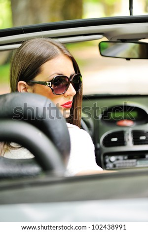 Portrait of young smiling woman siting behind steering wheel inside car - stock photo
