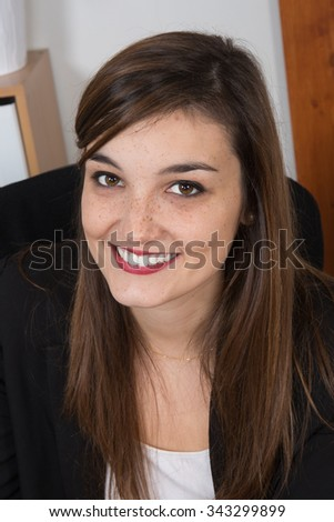 Portrait of young smiling woman sitting in her desk at office Close up.