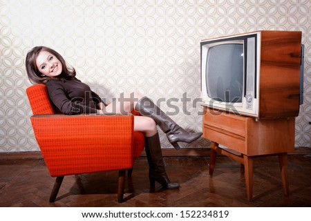 portrait of young smiling woman sitting in vintage room and watching tv, retro stylization, toned
