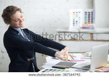 Portrait of young smiling woman wearing suit sitting at home office desk in front of laptop, stretching with enjoyment after the work is done, looking at screen with happy expression - stock photo
