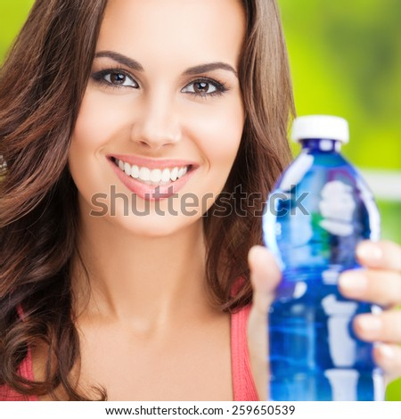 Portrait of young smiling woman with bottle of water, outdoor - stock photo