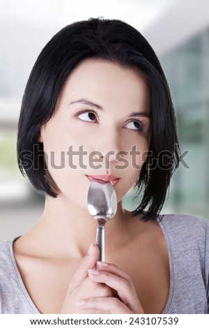Portrait of young smiling woman with spoon in her mouth - stock photo