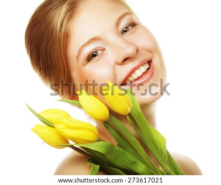 Portrait of young smiling woman with yellow tulips - stock photo