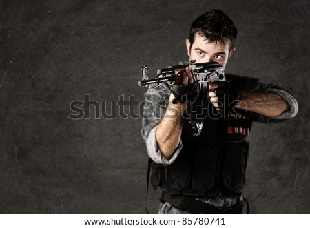 portrait of young soldier aiming with rifle against a grunge wall