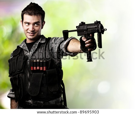 portrait of young soldier aiming with rifle against a wild background