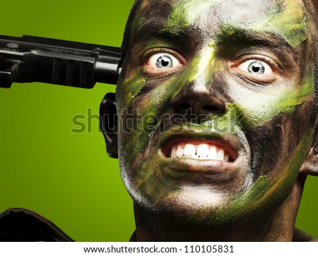 portrait of young soldier comitting suicide over green background - stock photo