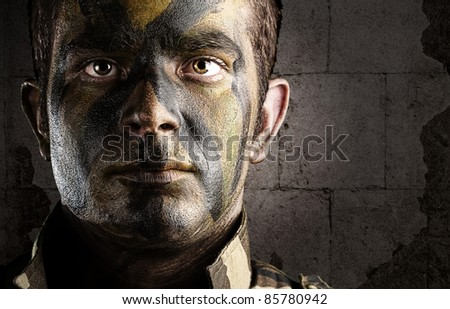 portrait of young soldier face painted with jungle camouflage against a grunge bricks wall - stock photo