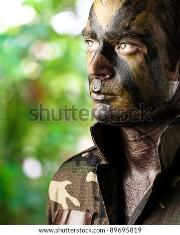 portrait of young soldier face painted with jungle camouflage in the jungle