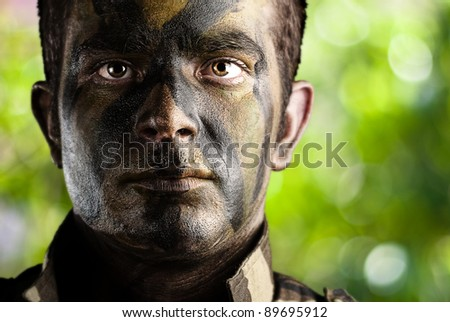 portrait of young soldier face painted with jungle camouflage in the jungle - stock photo