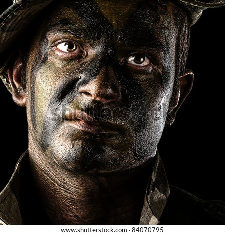 portrait of young soldier face with jungle camouflage over black background
