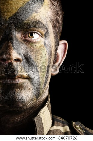 portrait of young soldier face with jungle camouflage paint against a black background - stock photo