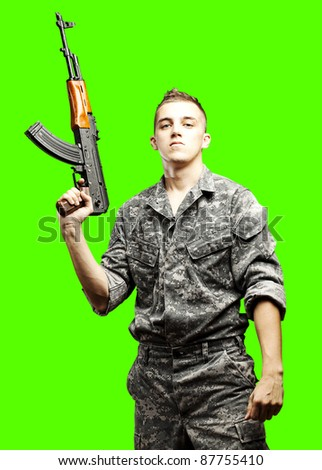 portrait of young soldier holding rifle against a removable chroma key background - stock photo